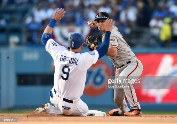 San Francisco Giants Second base Joe Panik turns to first as Los Angeles Dodgers Catcher Yasmani Grandal slides into second for the out during the...