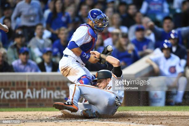 San Francisco Giants second baseman Joe Panik slides safely into home plate while Chicago Cubs catcher Willson Contreras attempts the force out to...