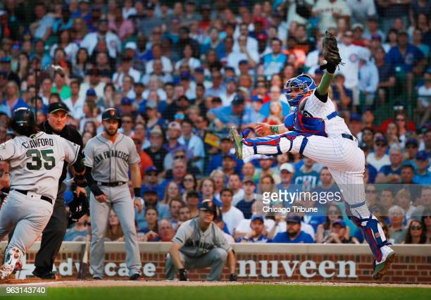 San Francisco Giants shortstop Brandon Crawford scores during the first inning while on the right is Chicago Cubs catcher Willson Contreras on Sunday...