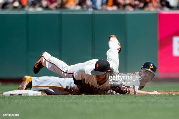 San Francisco Giants shortstop Brandon Crawford topples over the Pittsburgh Pirates' Gaby Sanchez right as Sanchez advanced to second base on a bunt...