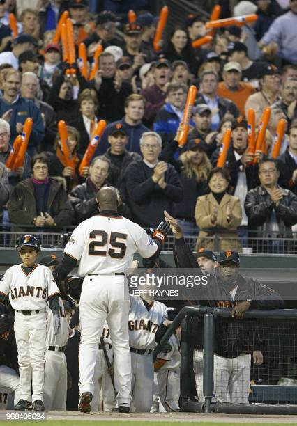 San Francisco Giants' slugger Barry Bonds is greeted at the dugout by manager Dusty Baker after he as brought home on a sacrifice fly by Reggie...