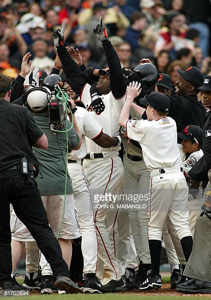 San Francisco Giants' slugger Barry Bonds is mobbed by teammates after hitting the game-winning two-run homerun in the 10th inning against the San...