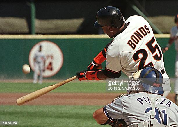 San Francisco Giants slugger Barry Bonds launches a threerun homerun against the Los Angeles Dodgers as catcher Mike Piazza looks on 18 September in...