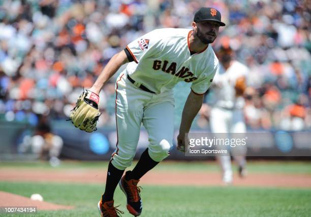 San Francisco Giants starting pitcher Andrew Suarez tosses a ball to first base for an out during the regular season game between the San Francisco...