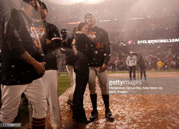 San Francisco Giants' starting pitcher Barry Zito and his wife Amber Seyer stand in the rain after beating the St. Louis Cardinals 9-0 to win Game 7...