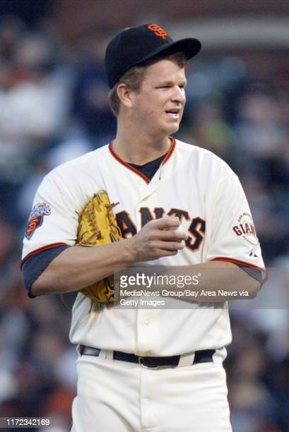 San Francisco Giants' starting pitcher Matt Cain pauses before pitching against Florida Marlins' Gaby Sanchez after Logan Morrison walked to first...