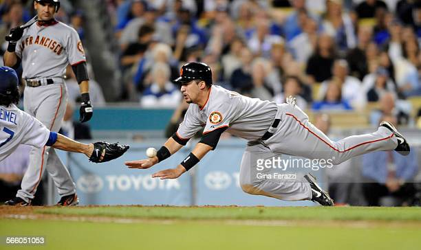San Francisco Giants Travis Ishikawa scores on a wild pitch as Dodgers pitcher Joe Beimel can't get a glove on the ball to make the tag in the fifth...