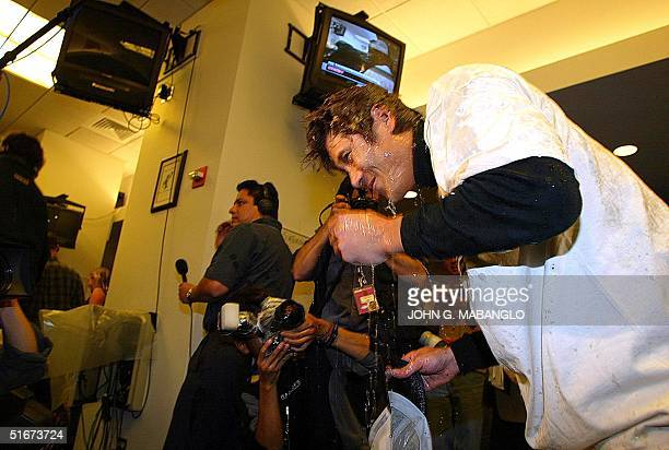 San Francisco Giants' Tsuyoshi Shinjo of Japan drips after being doused with champagne by teammates in the clubhouse after the Giants clinched the...