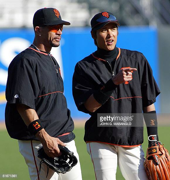 San Francisco Giants' Tsuyoshi Shinjo of Japan talks with teammate Benito Santiago during practice at Pacific Bell Park 21 October 2002 in San...