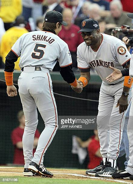 San Francisco Giants Tsuyoshi Shinjo shakes hands with team manager Dusty Baker before Game One of the World Series against the Anaheim Angels in...