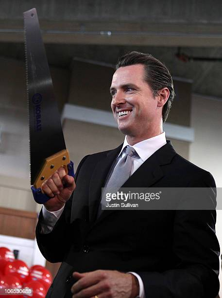 San Francisco mayor and California Lt Governorelect Gavin Newsom holds a hand saw during a ribbon cutting during the grand opening of the Lowe's...