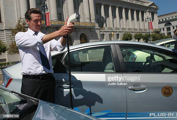 San Francisco mayor Gavin Newsom holds a power cable before test driving a plugin version of the popular Toyota Prius that is one of four on loan to...
