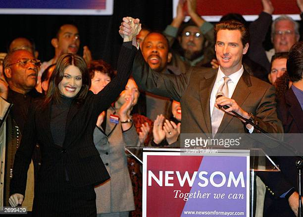 San Francisco mayoral candidate Gavin Newsom lifts arms with his wife Kimberly Guilfoyle Newsom before speaking to supporters at an election night...