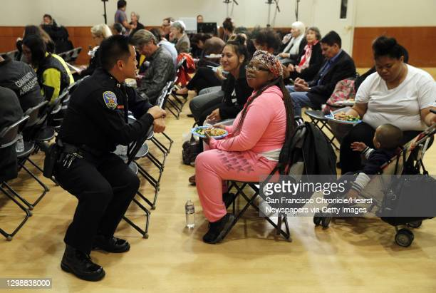 San Francisco Police Dept. Capt. Paul Yep chats wtih Ashley Bell, center, before a police commission meeting at Grace Cathedral in San Francisco,...