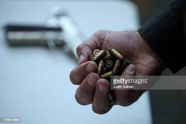 San Francisco police officer holds a handful of ammunition that was surrendered during a gun buyback event on August 8 2013 in San Francisco...