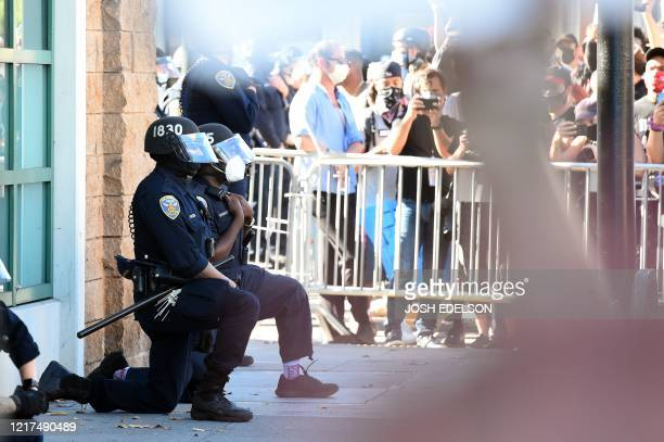 """San Francisco police officers kneel after a crowd of protesters called for them to """"take a knee"""" in front of a police station in San Francisco,..."""
