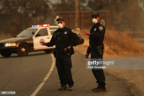 San Francisco police officers Malek Jisrawi and Sterling Hayes flag down a passing truck at a road closure checkpoint on October 16, 2017 in Glen...