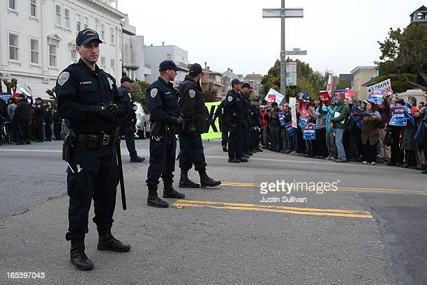 San Francisco police officers stand watch as demonstrators protest near the site of a fundraiser on April 3 2013 in San Francisco California Hundreds...