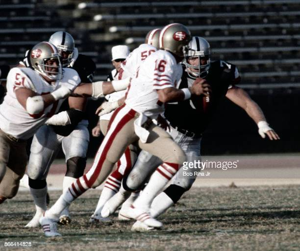 San Francisco quarterback Joe Montana scrambles to avoid LA Raider's Howie Long during San Francisco 49'ers game against Los Angeles Raiders August 6...