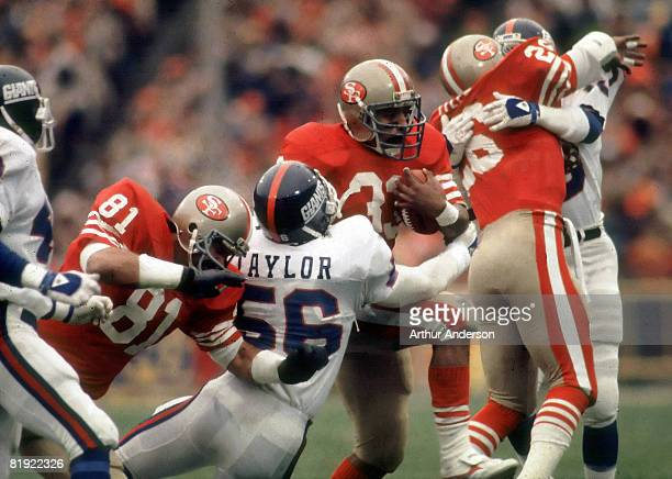 San Francisco running back Roger Craig tries to run through New York Giants Hall of Fame linebacker Lawrence Taylor as tight end Russ Francis and...