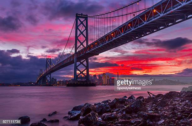 san francisco skyline and bay bridge at sunset - bay bridge stock pictures, royalty-free photos & images