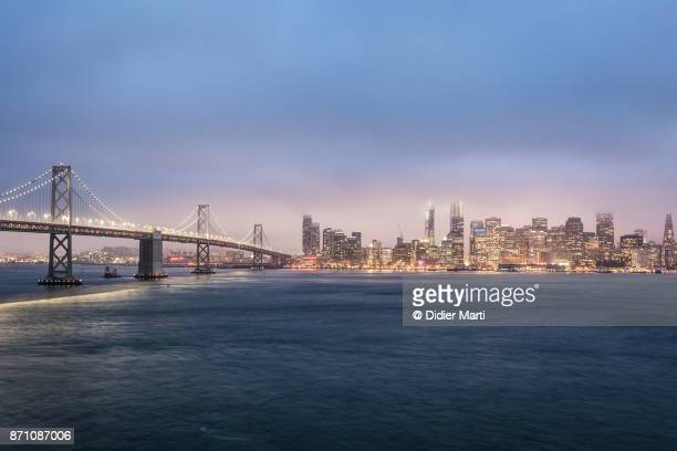 san francisco skyline and the san francisco auckland bay bridge view from treasure island - bay bridge stock pictures, royalty-free photos & images