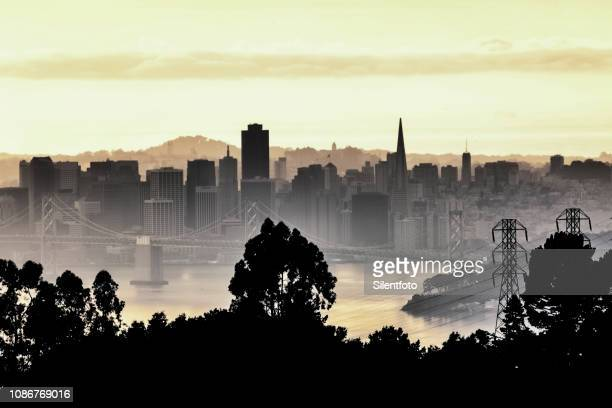 san francisco skyline behind silhouetted ridge line - oakland california skyline stock pictures, royalty-free photos & images