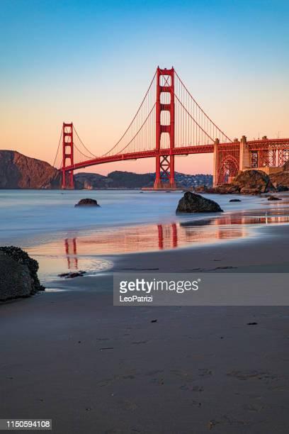 san francisco-die golden gate bridge bei sonnenuntergang vom strand - san francisco stock-fotos und bilder