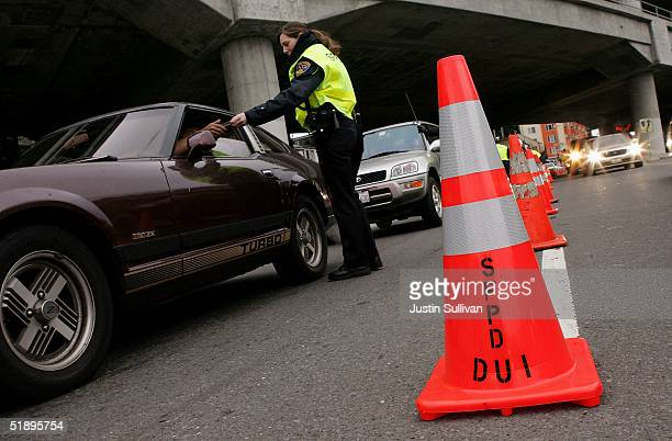 San Franciso police officer checks a drivers license at a sobriety checkpoint December 26 2004 in San Francisco California The California Highway...