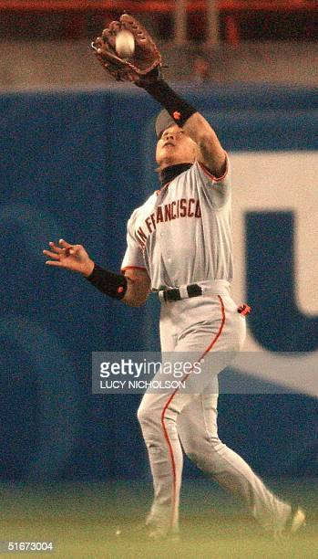 San Fransisco Giants' Japanese player Tsuyoshi Shinjo catches out Los Angeles Dodgers' Shawn Green in the bottom of the first inning in Los Angeles...