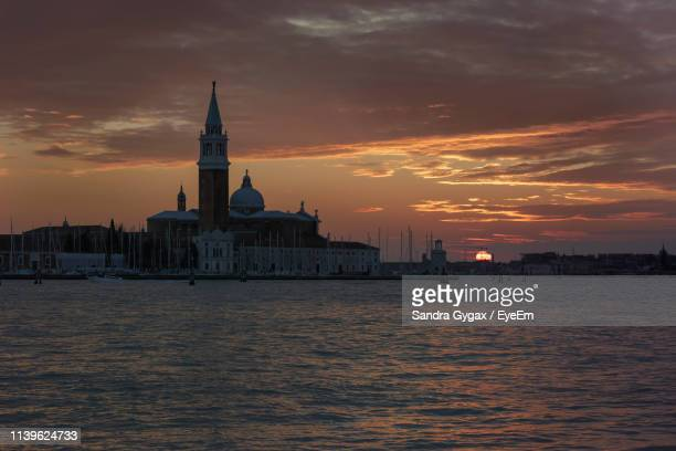 san giorgio maggiore by grand canal against cloudy sky during sunset - sandra gygax stock-fotos und bilder