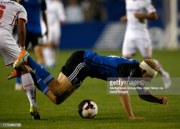San Jose Earthquakes' Steven Lenhart gets knocked to the ground against Deportivo Toluca FC's Miguel Ponce in the second half at Buck Shaw Stadium in...