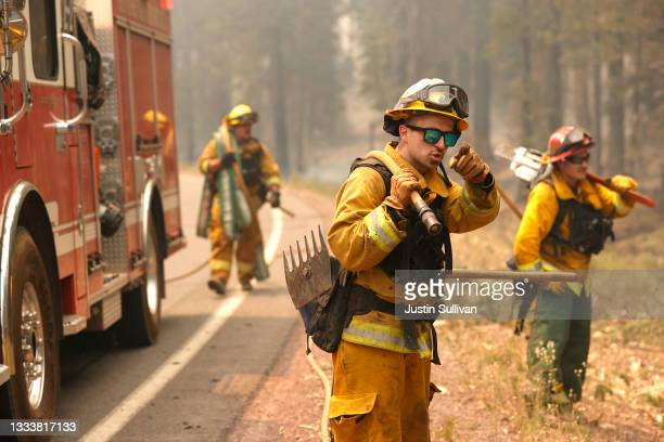 San Jose firefighter Ryan Godoy point out hot spots to his colleagues while battling the Dixie Fire on August 12, 2021 near Westwood, California. The...