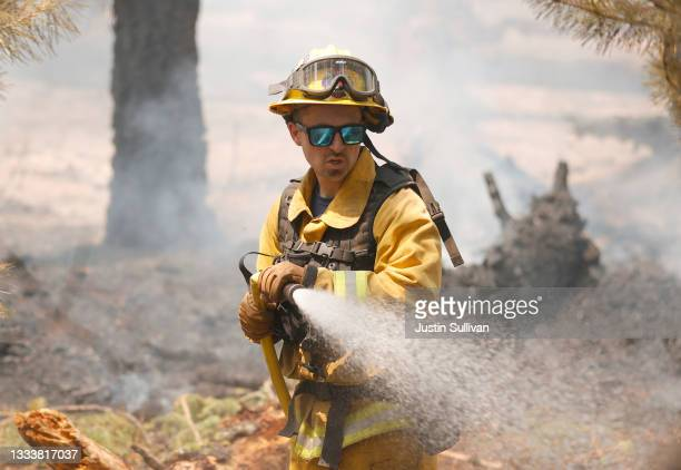 San Jose firefighter Ryan Godoy uses a hose to extinguish hot spots while battling the Dixie Fire on August 12, 2021 near Westwood, California. The...