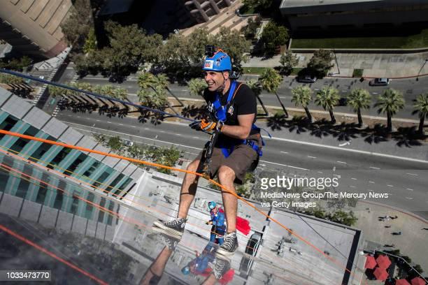 San Jose Mayor Sam Liccardo, foreground, and Sunnyvale Mayor Glenn Hendricks, background, rappel down the Adobe headquarters building during the 2nd...