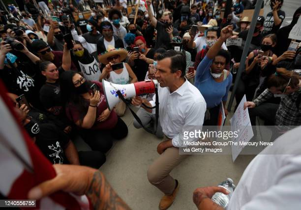San Jose Mayor Sam Liccardo speaks to protesters as he takes a knee during a protest of the killing of George Floyd outside of San Jose City Hall in...