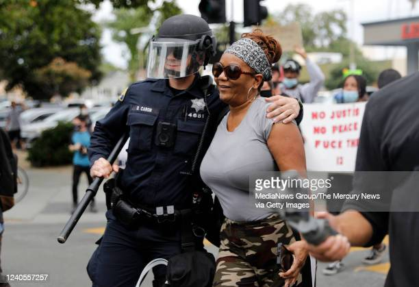 San Jose Police officer gives a protester a hug during a protest for the killing of George Floyd outside of San Jose City Hall in downtown San Jose...