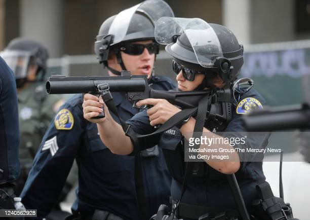San Jose Police officer prepares to fire a rubber bullet at a protester during a protest for the killing of George Floyd outside of San Jose City...