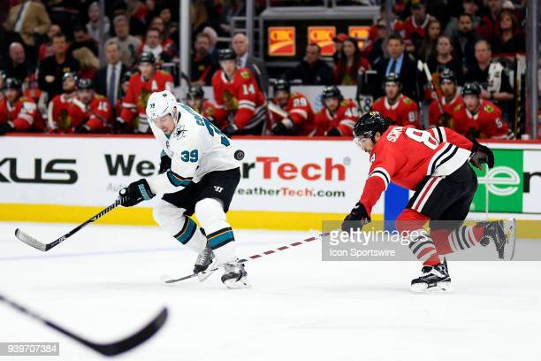 San Jose Sharks center Logan Couture battles with Chicago Blackhawks center Nick Schmaltz in action during a game between the Chicago Blackhawks and...