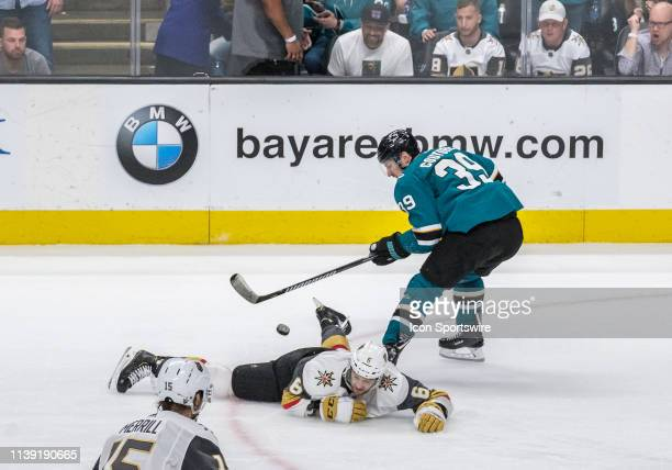 San Jose Sharks center Logan Couture tries to get the puck away from downed Vegas Golden Knights defenseman Colin Miller during overtime in Game 7...