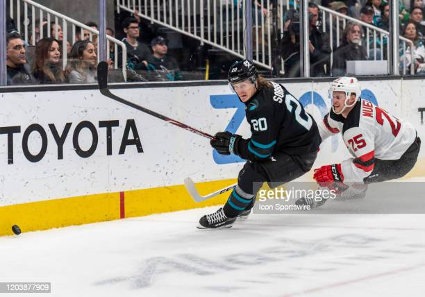 San Jose Sharks left wing Marcus Sorensen moves around the boards behind the goal with New Jersey Devils defenseman Mirco Mueller in pursuit during...