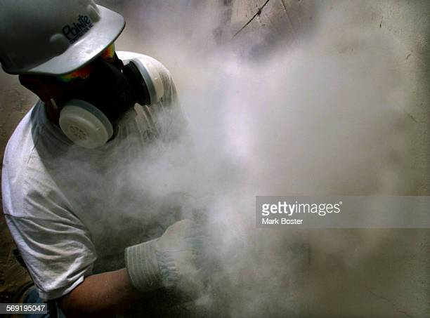 San Juan Capistrano––A worker is enveloped in a cloud of dust as he cut his way through history slicing into an adobe archway at Mission San Juan...