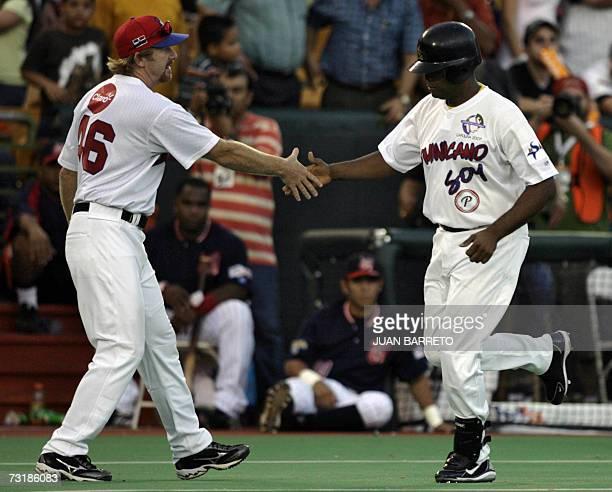 Tony Batista de las Aguilas Cibaenas de Republica Dominicana festeja junto al coach tras batear home run en un juego contra los Tigres de Aragua de...