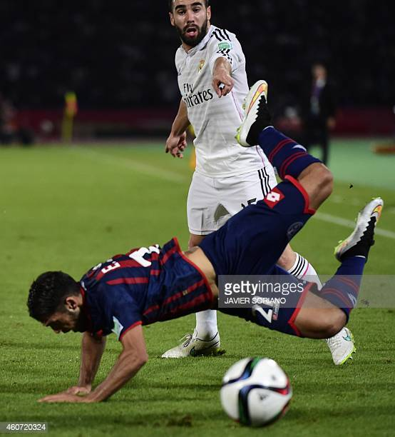 San Lorenzo's defender Emmanuel Mas falls while confronting Real Madrid's defender Dani Carvajal during their FIFA Club World Cup final football...