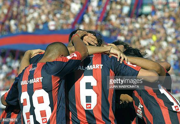 San Lorenzo's Martin Morel celebrates with teammates Cristian Ledesma and Santiago Solari after scoring a goal against Tigre during their Argentine...