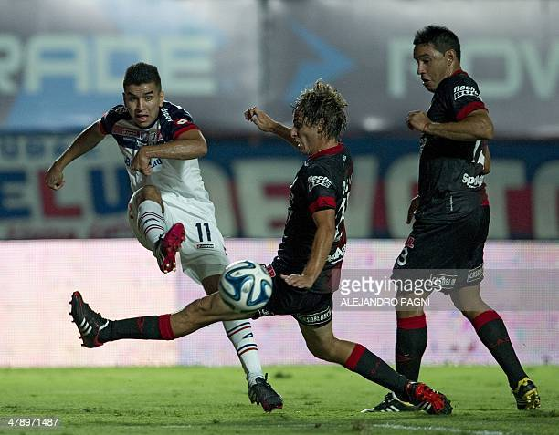 San Lorenzo's midfielder Angel Correa kicks the ball next Colon's defender Mariano Bittolo during their Argentine First Division football match at...