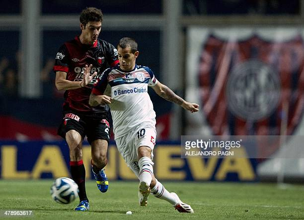 San Lorenzo's midfielder Leandro Romagnoli vies for the ball with Colon's forward Lucas Alario during their Argentine First Division football match...