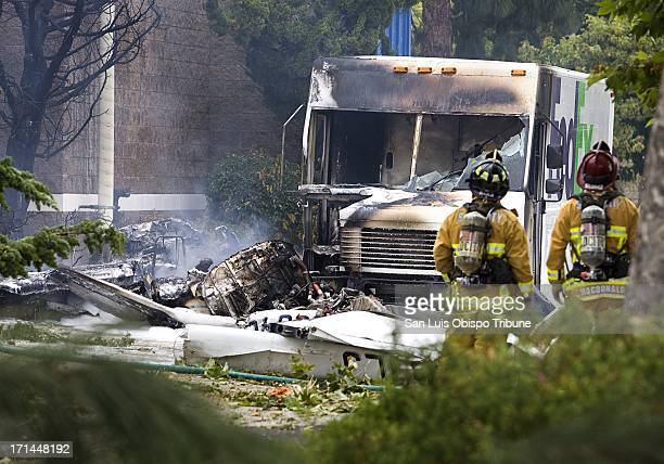 San Luis Obispo City firefighters look at the remnants of a plane that crashed into a FedEx truck Monday June 24 in San Luis Obispo California