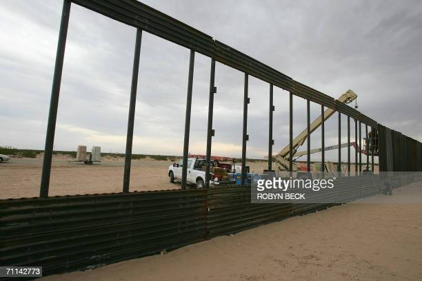 Members of the 116th Construction Equipment Support Company of the Utah National Guard extend a wall along the US border with Mexico to prevent...