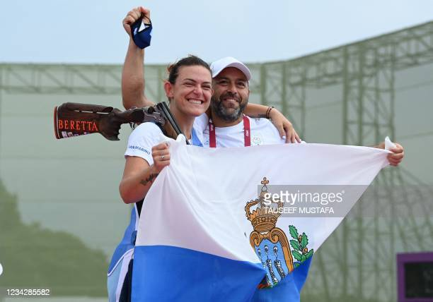 San Marino's Alessandra Perilli poses with her coach and national flag after winning the bronze medal in the women's trap final during the Tokyo 2020...